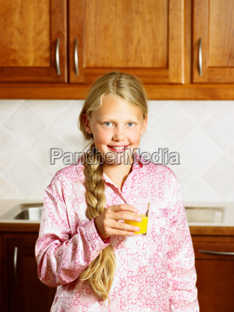 young girl holding orange juice