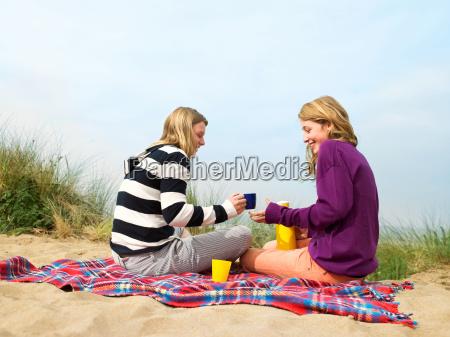 women drinking hot drink on blanket