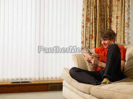 young man relaxing on sofa reading