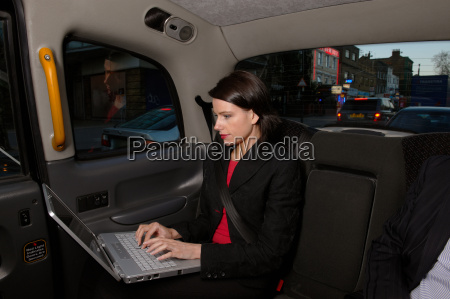 business woman with laptop in taxi