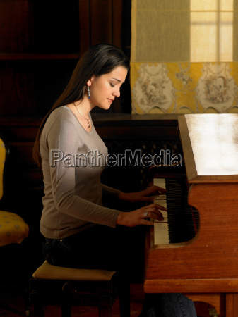 young woman playing piano side view