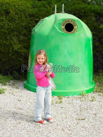 young girl standing by recycling bin