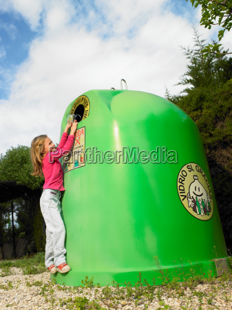 young girl putting bottle in recycling