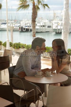 loving couple sitting outside cafe