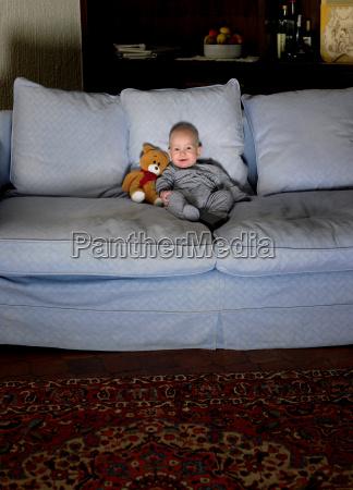 baby boy sitting on sofa