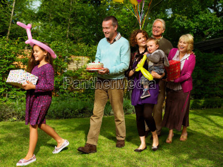 family arriving with birthday cake