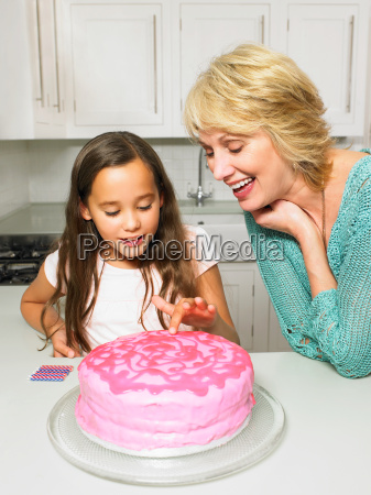 senior woman and girl with cake