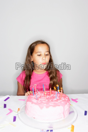girl blowing out candles on cake