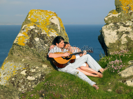 young couple on a cliff playing