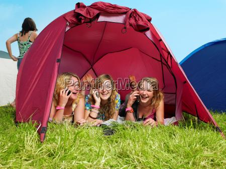 three girls lying in tent