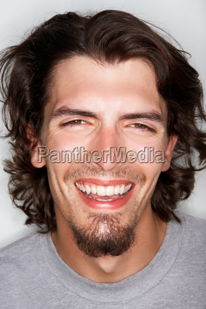 young male with long hair smiling