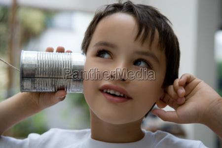boy using a tin can as