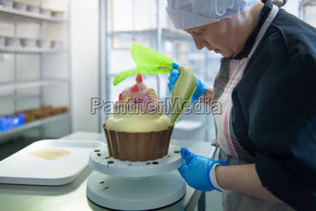 chocolatier icing large cup cake in