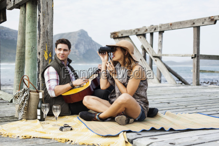 young couple picnicing on old pier