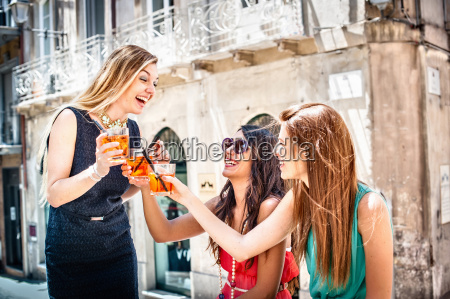three young fashionable female friends toasting
