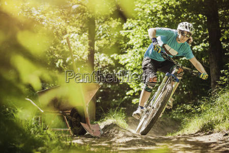 young female mountain biker riding forest