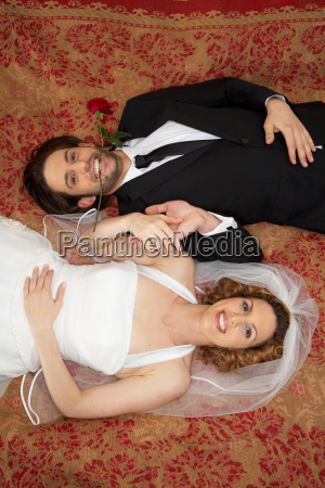 young bridal couple smiling on bed