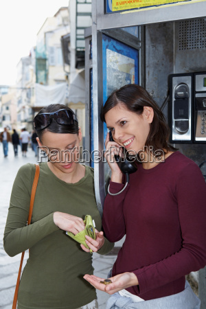 two young girls on public phone