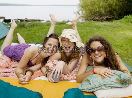 three women laying on blankets smiling