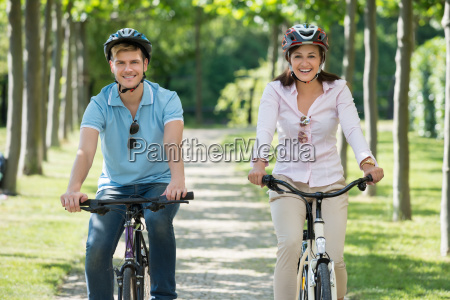 happy young couple biking in park