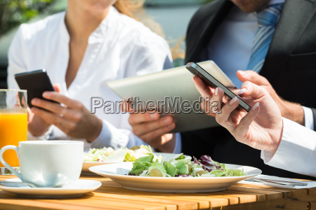 close up of businesspeople using digital