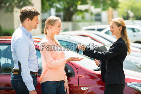 dealer giving car key to couple