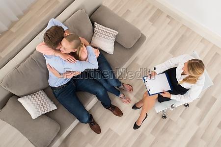 paar sitzt auf sofa umarmen vor