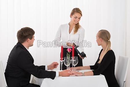 waitress suggesting bottle of wine to