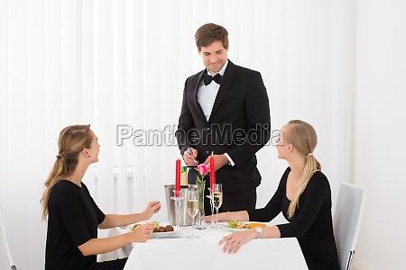 kellner nimmt eine bestellung von freundinnen