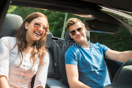 young couple in a car wearing