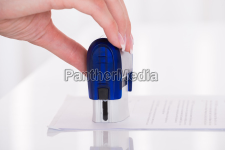 persons hand stamping document