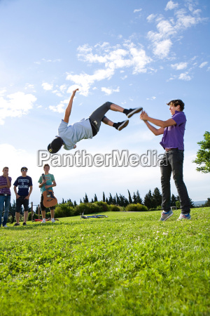 teen boys help friend to do
