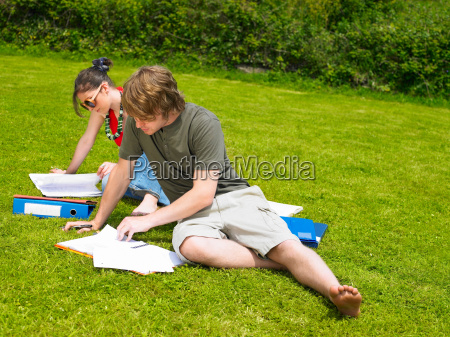 two young people studying on lawn