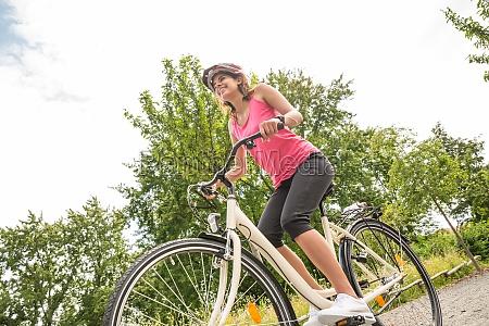 gluecklicher weiblicher radfahrer reitfahrrad