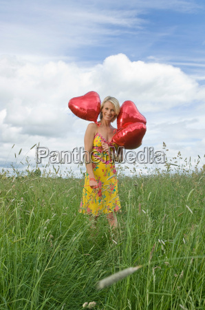smiling woman in field with balloons