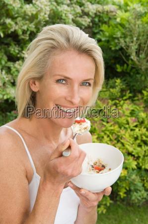 woman eating fruit and muesli