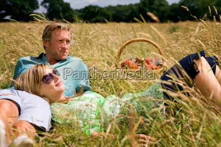 couple laying field with picnic basket