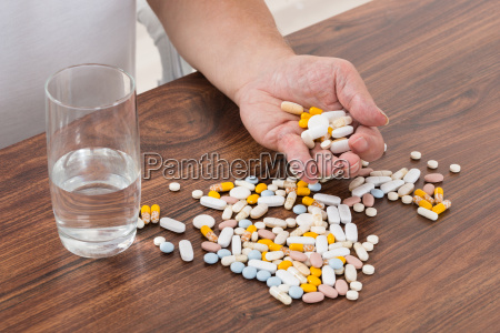 persons hand holding pills