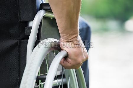 behinderte menschen pushing wheel of rollstuhl