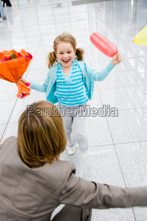 girl holding flowers running at woman