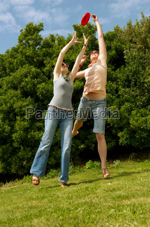 two, women, jumping, to, catch, a - 18270508