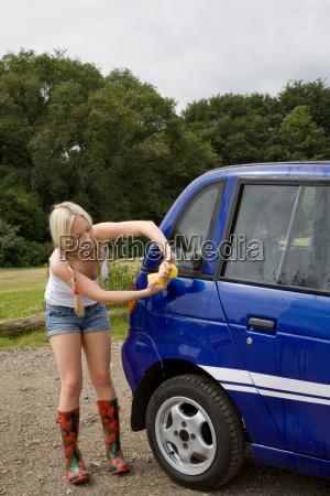 young woman washing electric car