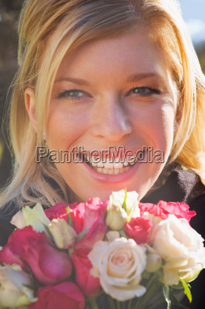a female smiling holding some roses