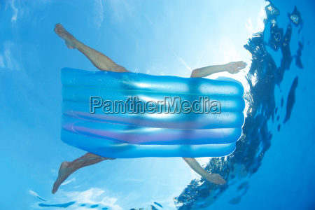 man on inflatable lilo in pool