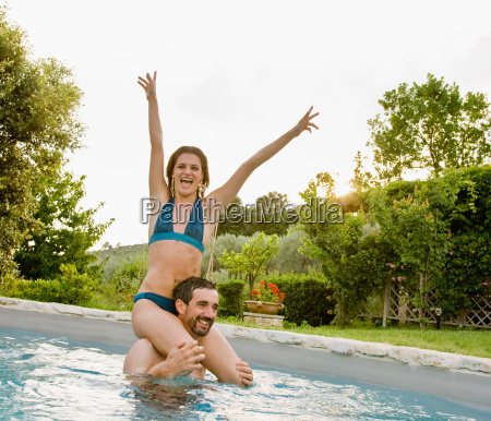 couple enjoying sun in pool