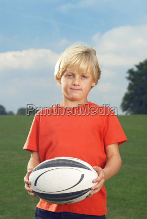 boy holding rugby ball in filed