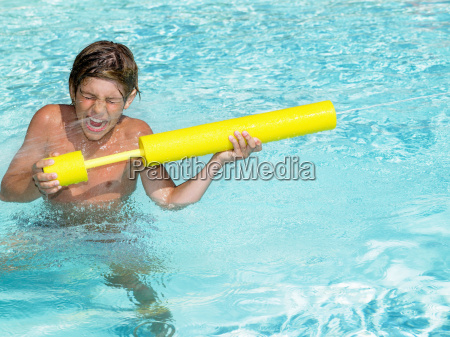 boy playing with water gun in