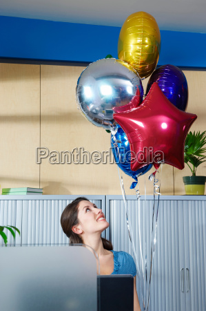 young woman with balloons at desk