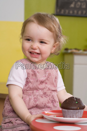 young girl on table with muffin