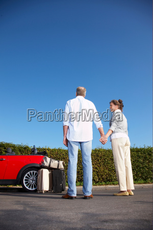 couple holding hands by car